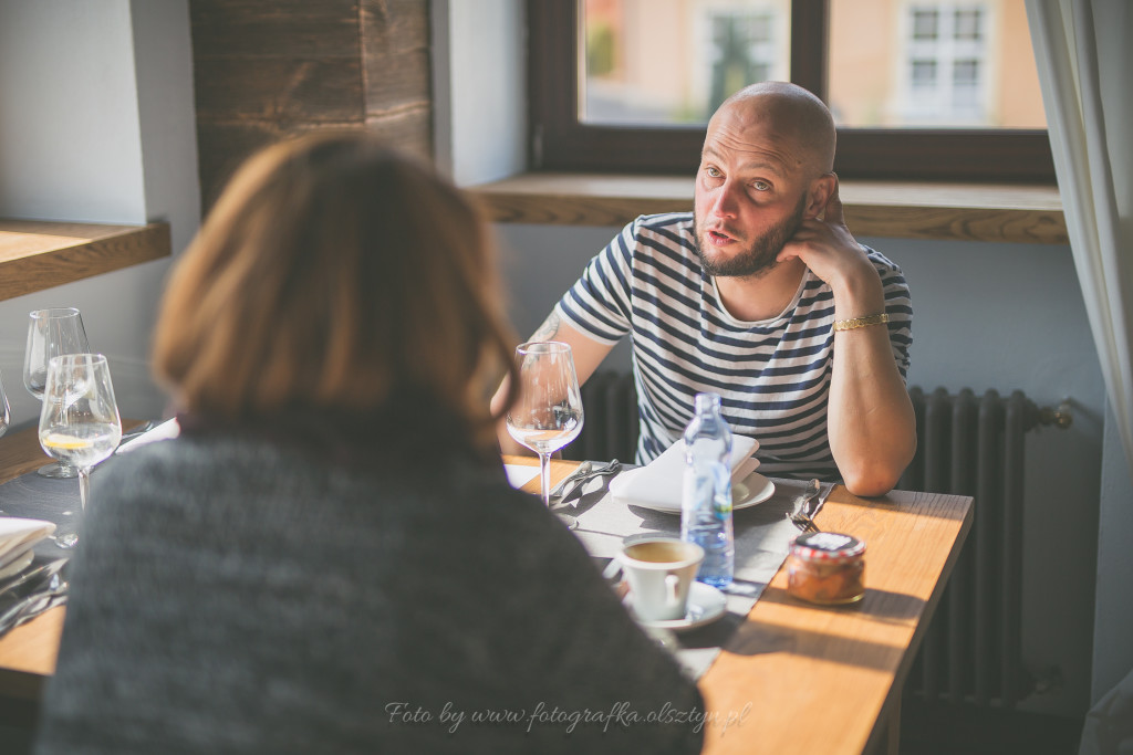 Jarek Poliwko siedzi przy stole wraz autorką bloga